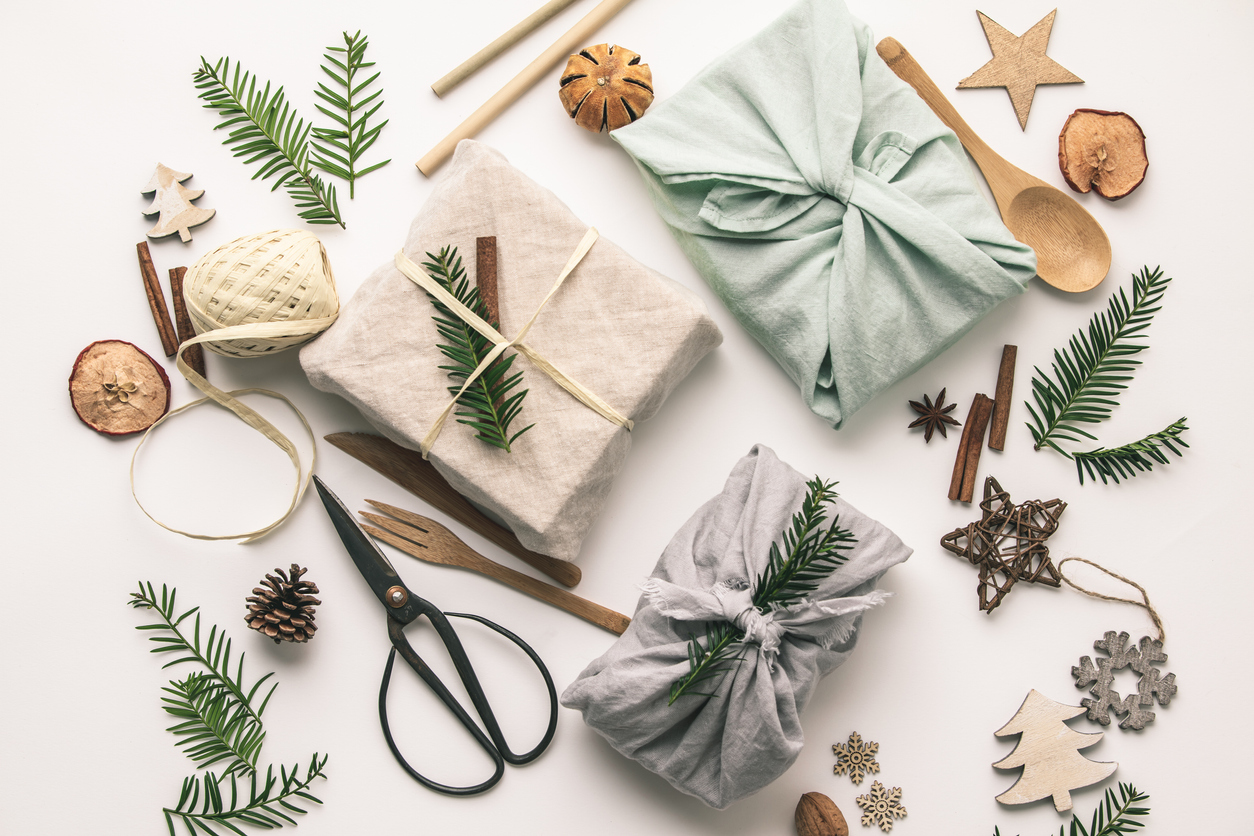 Fabric wrapped gifts and wooden Christmas decorations, reusable sustainable recycled textile gift wrapping alternative zero waste concept, flat lay, top view